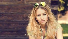 Portrait de femme blonde au mur en bois Photographie stock