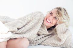 Portrait de femme blonde dans le chandail beige se situant dans le lit image libre de droits