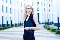 Portrait de femme blonde intelligente avec un carnet sur le fond du centre d'affaires Photographie stock libre de droits