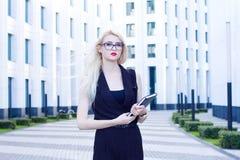 Portrait de femme blonde intelligente avec un carnet sur le fond du centre d'affaires Images libres de droits