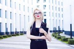 Portrait de femme blonde intelligente avec un carnet sur le fond du centre d'affaires Image libre de droits