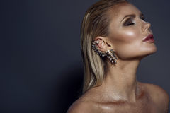 Portrait de femme blonde magnifique chic avec les cheveux humides, le maquillage éclatant artistique et la manchette sur son orei image stock