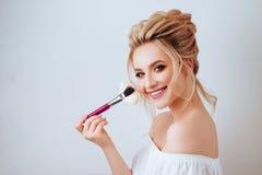 Portrait de femme blonde de sourire heureuse avec la longue brosse onduleuse de participation de coiffure images stock