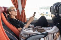 Portrait de femme conduisant sur l'autobus mobile se reposant par la fenêtre utilisant le téléphone portable photographie stock