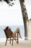 Portrait de femme détendant sur la chaise longue par la piscine d'infini Photo stock