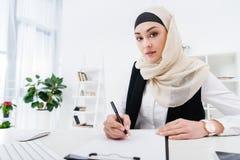 portrait de femme d'affaires arabe regardant l'appareil-photo tout en signant des papiers Photos stock