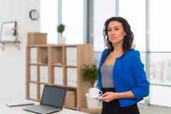 Portrait de femme d'affaires dans le bureau semblant sûr et le sourire Photo stock