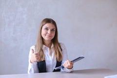 Portrait de femme d'affaires montrant le geste et tenant des WI de dossier Photographie stock libre de droits
