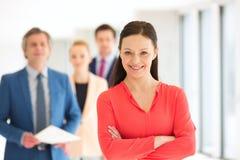 Portrait de femme d'affaires sûre avec l'équipe à l'arrière-plan au bureau Photos libres de droits