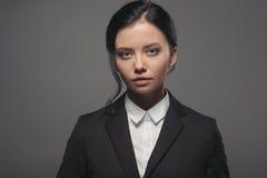 Portrait de femme d'affaires sûre de brune dans la veste noire regardant l'appareil-photo Image stock