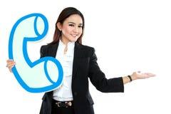 Portrait de femme d'affaires tenant le signe du téléphone et de la représentation Photo stock