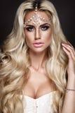 Portrait de femme d'isolement sur le fond foncé Jeune fille blonde posant avec des bijoux sur la tête Images stock