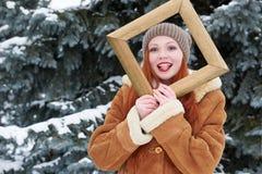Portrait de femme dans le cadre en bois de photo à la saison d'hiver Temps de Milou en parc d'arbre de sapin Photos stock