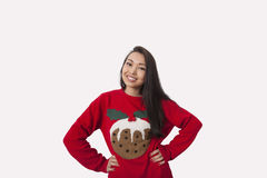 Portrait de femme dans le chandail de Noël se tenant avec des mains sur des hanches au-dessus de fond gris images stock