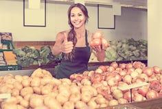 Portrait de femme dans le tablier vendant les oignons non épluchés Photo stock
