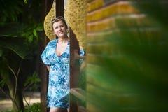 Portrait de femme dans une robe bleue, qui se tient à la porte de sa maison pendant l'été et les invités de attente photos stock