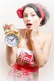 Portrait de femme de pin-up de jeunes yeux bleus drôles agitated de brune avec le réveil regardant l'appareil-photo Photographie stock libre de droits