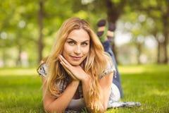 Portrait de femme de sourire avec des mains sur le menton se trouvant sur l'avant Photographie stock libre de droits
