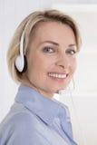 Portrait de femme de sourire avec l'écouteur sur la vente par téléphone. Photo libre de droits