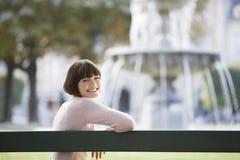 Portrait de femme de sourire en Front Of Blurred Fountain Image stock