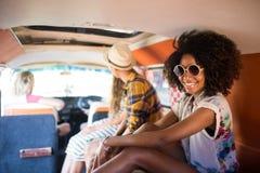 Portrait de femme de sourire se reposant avec des amis dans le camping-car Photos stock