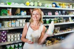 Portrait de femme de sourire tenant la bouteille avec du lait frais Photographie stock libre de droits