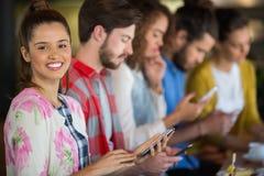 Portrait de femme de sourire tenant le téléphone portable tout en se reposant avec des amis Photographie stock libre de droits