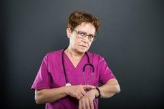 Portrait de femme docteur supérieure montrant la montre-bracelet Images libres de droits
