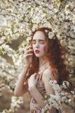 Portrait de femme douce d'A avec de longs cheveux rouges dans un jardin de floraison de ressort Fille sensuelle rousse avec la pe photos libres de droits