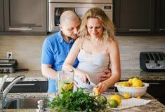 Portrait de femme enceinte de sourire de personnes caucasiennes blanches des couples deux avec le mari faisant cuire la nourritur Photos stock