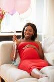 Portrait de femme enceinte détendant sur Sofa Holding Balloons Image libre de droits