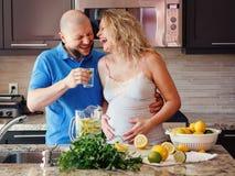 Portrait de femme enceinte riante de sourire de personnes caucasiennes blanches des couples deux avec le mari faisant cuire la no Image stock