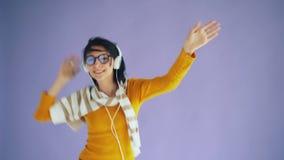 Portrait de femme enthousiaste dans des écouteurs dansant écouter de refroidissement la musique clips vidéos