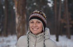 Portrait de femme espiègle dans le sourire tricoté de chapeau d'hiver Images libres de droits
