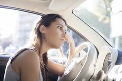 Portrait de femme fatiguée conduisant la voiture images stock