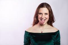 Portrait de femme folle drôle avec les taches de rousseur et la robe verte classique avec la langue photo libre de droits