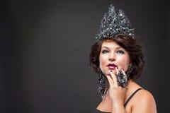 Portrait de femme futée avec une couronne magnifique, des boucles d'oreille et des anneaux photos libres de droits