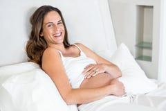 Portrait de femme gaie détendant sur le lit Photo stock