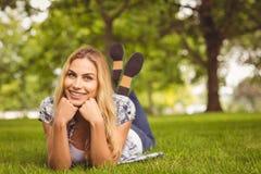 Portrait de femme heureuse avec des mains sur le menton au parc Photographie stock