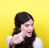 Portrait de femme heureuse avec des pouces sur le fond jaune Photographie stock