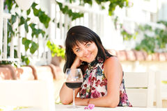 Portrait de femme heureuse avec le verre de vin rouge en café Photos stock
