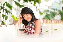 Portrait de femme heureuse avec le verre de vin rouge en café Images stock