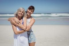 Portrait de femme heureuse avec sa mère se tenant à la plage images stock