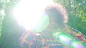 Portrait de femme heureuse d'afro-américain avec la coiffure d'Afro dans la chemise et des écouteurs MOIS lent banque de vidéos