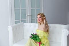 Portrait de femme heureuse dans la robe jaune avec le bouquet de tulipe sur le divan Image stock