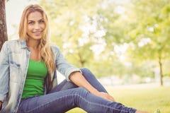 Portrait de femme heureuse se reposant sous l'arbre Image stock