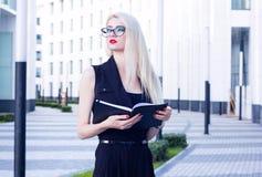 Portrait de femme intelligente avec un carnet ouvert sur le fond du centre d'affaires Photo stock