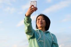 Portrait de femme japonaise sensuelle avec les cheveux courts prenant à selfie extérieur utilisant elle le téléphone Fond bleu de Images libres de droits