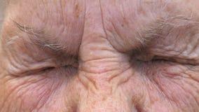 Portrait de femme mûre vissant vers le haut de ses yeux gris et puis ouvert Fermez-vous vers le haut du visage froissé de la viei banque de vidéos