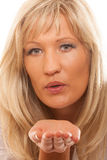 Portrait de femme mûre soufflant un baiser d'isolement Photographie stock